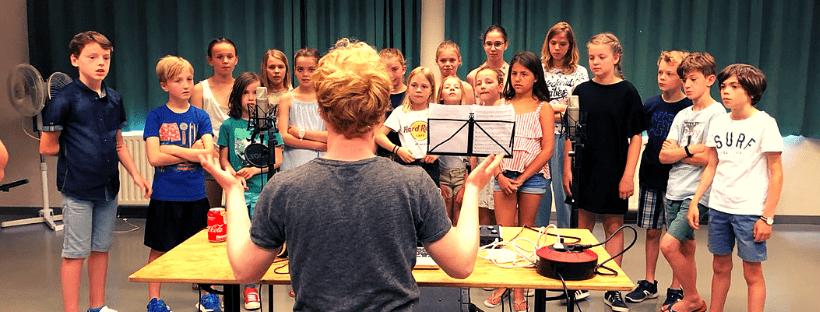 Het opnemen van een schoollied samen met de componist